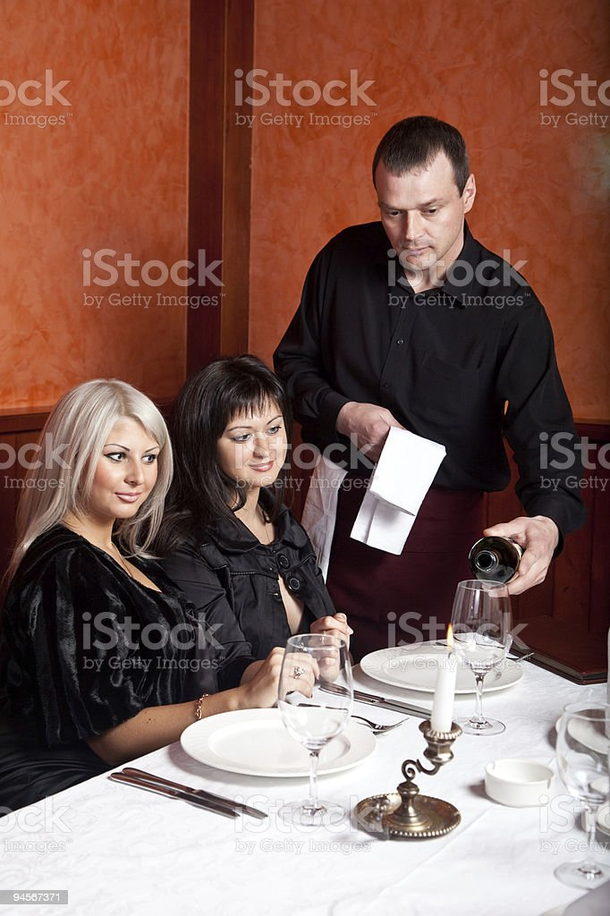 Waiter at the restaurant offers wine visitors royalty-free stock photo