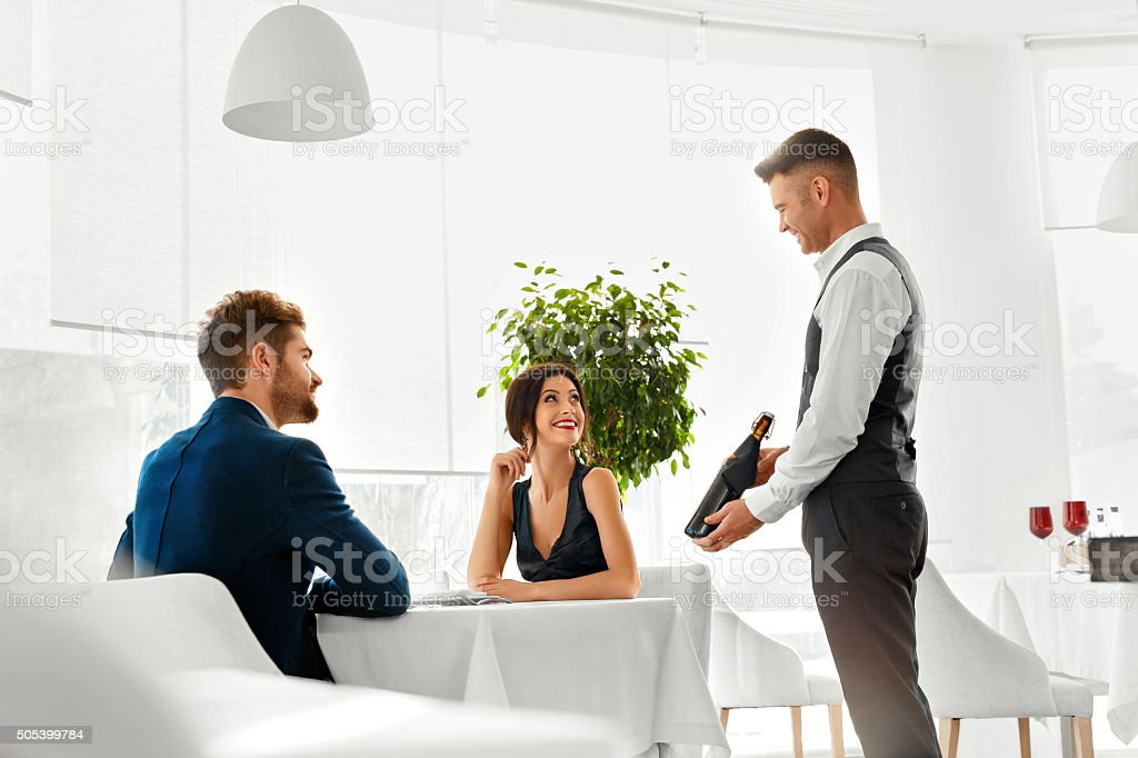 Waiter Bringing Wine Bottle To Couple In Love. Romantic Dinner. stock photo