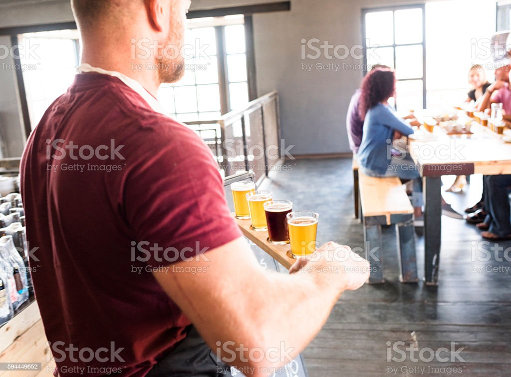Waiter Carrying A Tray Of Beer Tasting Glasses stock photo