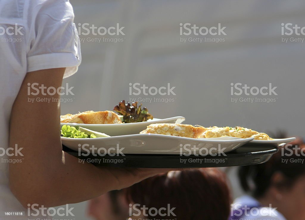 Waiter carrying plates of food to customers stock photo