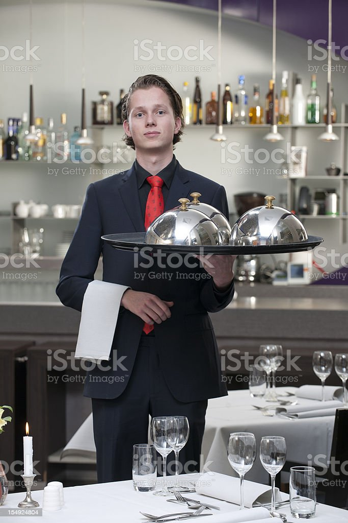 waiter carrying serving tray in restaurant XXXL image stock photo