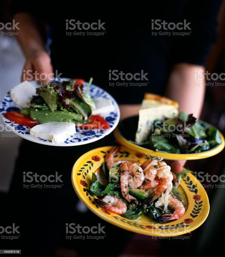 A waiter carrying three colorful plates of tapas royalty-free stock photo