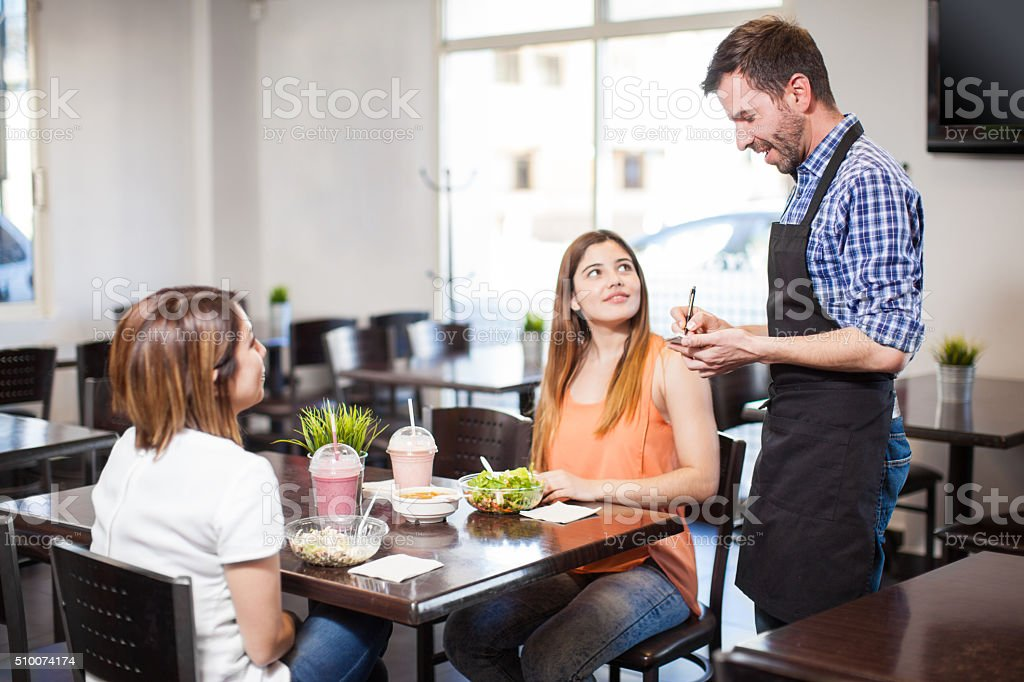Waiter checking up on his customers stock photo