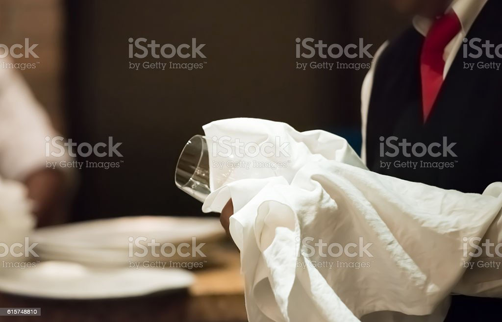 Waiter cleaning glass stock photo