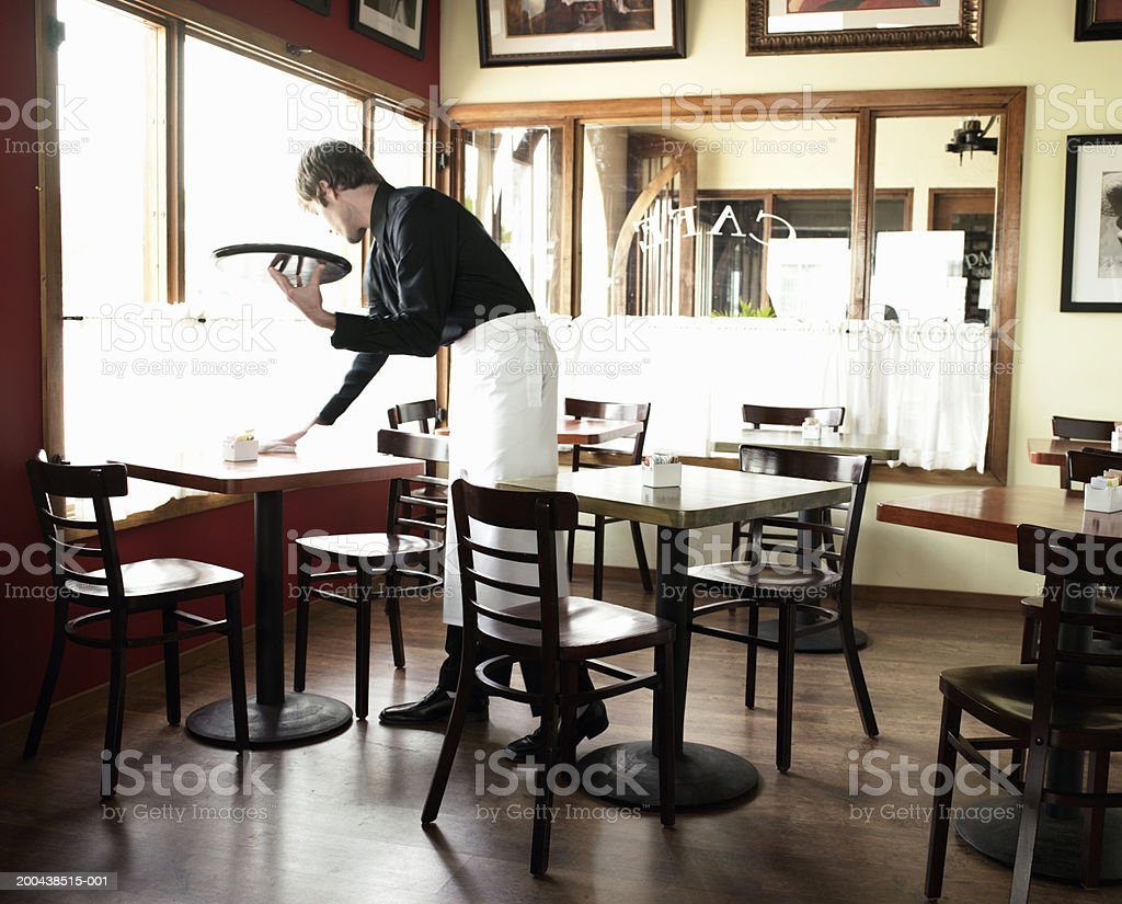 Waiter cleaning table in coffee shop stock photo