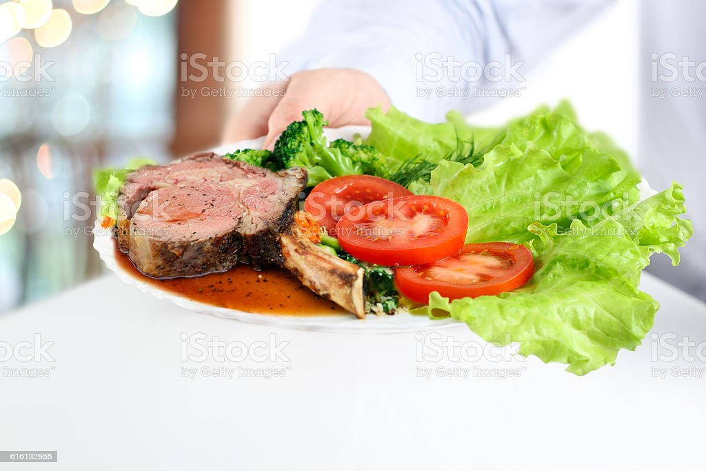 Waiter giving a steaks and vegetables on a plate stock photo