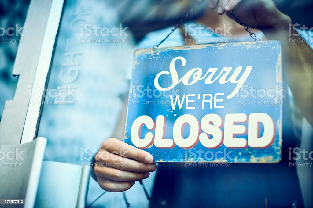 Waiter hanging closed sign on glass window stock photo