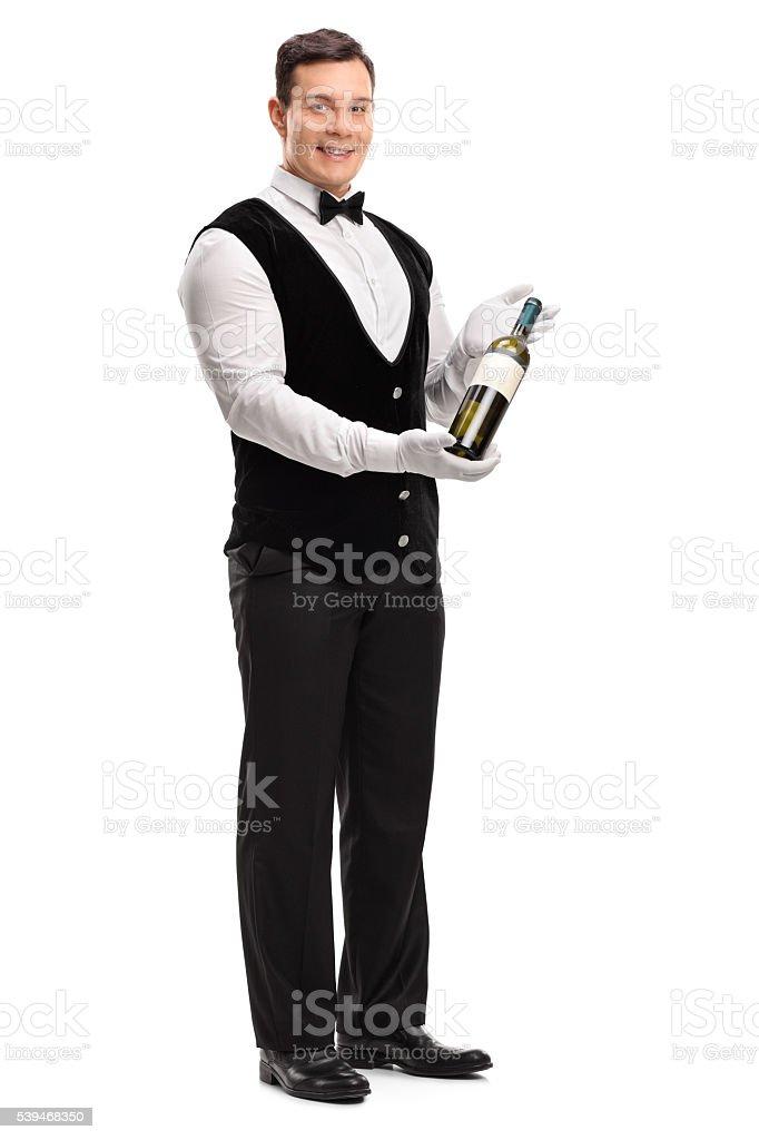 Waiter holding a bottle of white wine stock photo