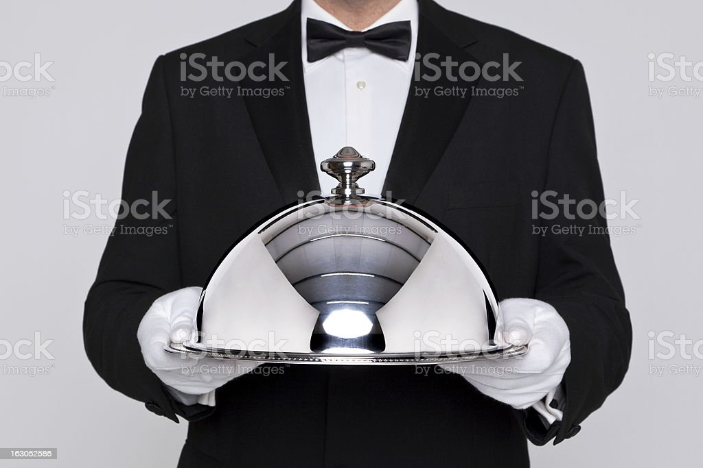 Waiter holding a silver cloche royalty-free stock photo