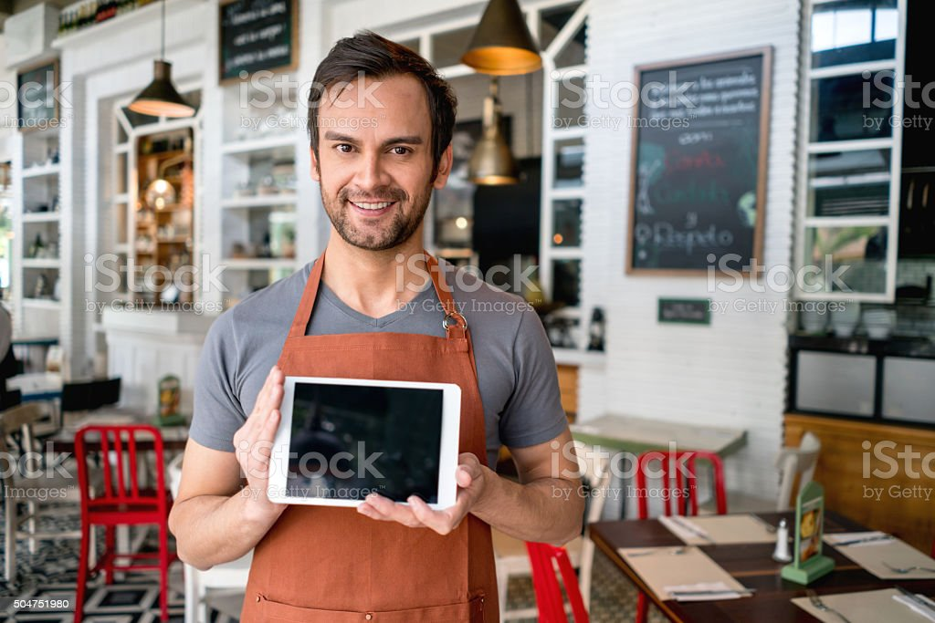 Waiter holding a tablet computer at the restaurant stock photo