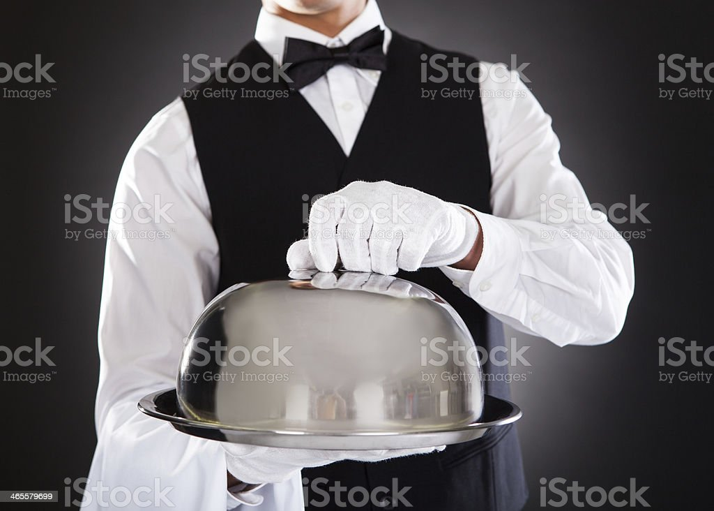 Waiter holding a tray with a lid getting ready to open it stock photo