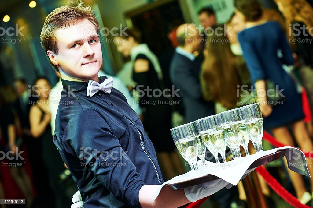 Waiter holding a tray with glasses of vine stock photo