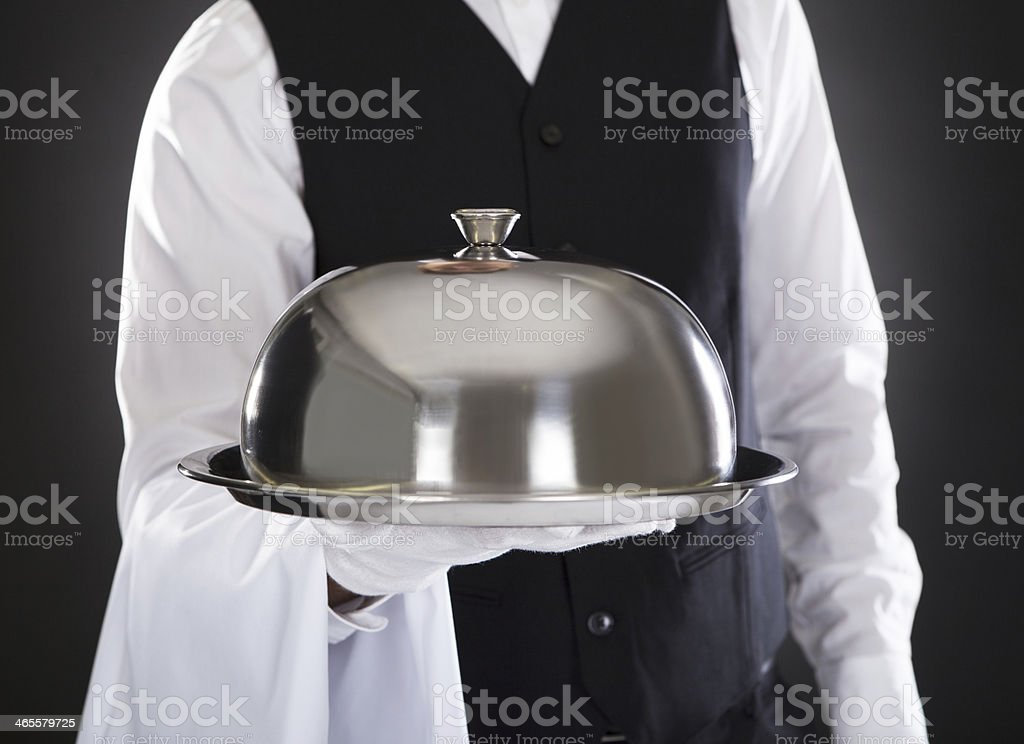 A waiter holding a tray with lid royalty-free stock photo