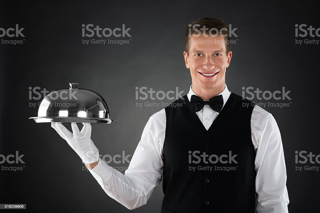 Waiter Holding Cloche Over Tray stock photo