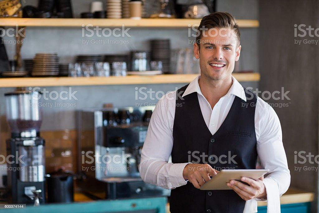 Waiter holding digital tablet in restaurant stock photo
