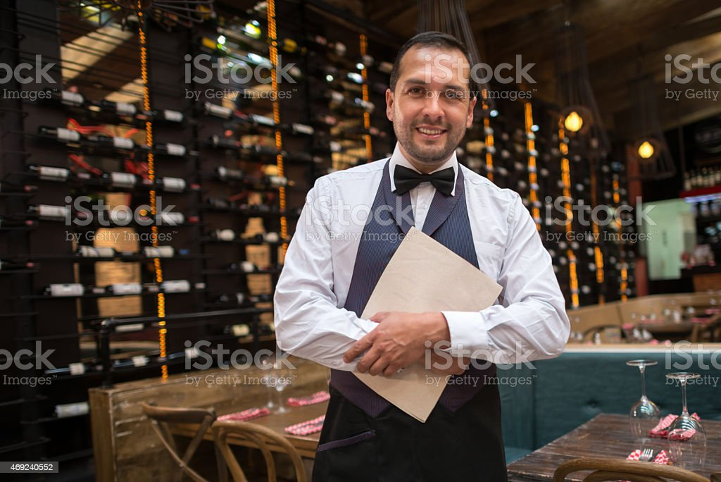 Waiter holding menu at a restaurant stock photo