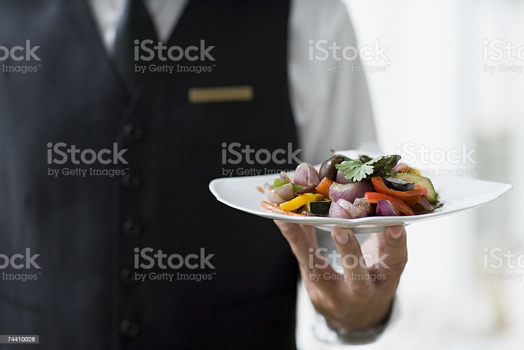Waiter holding plate stock photo