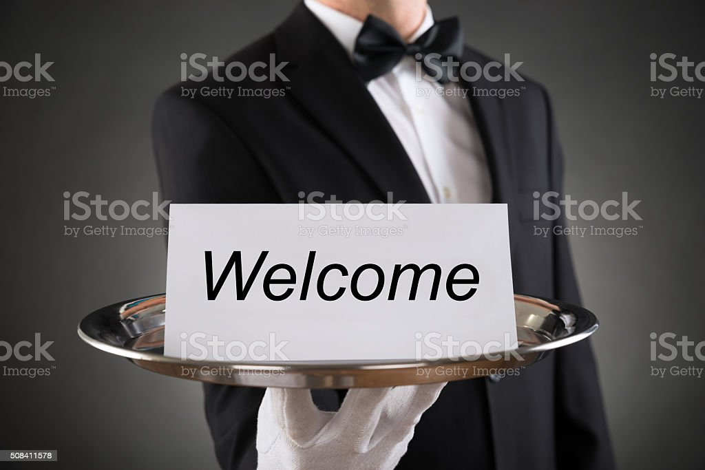 Waiter Holding Plate With Welcome Text On Paper stock photo