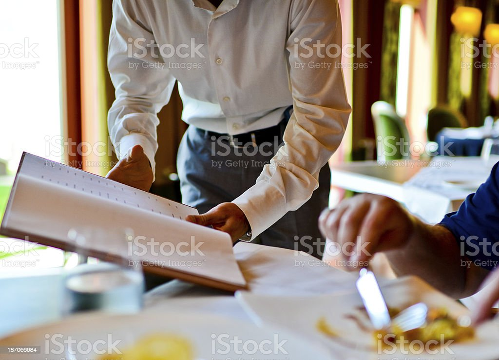 Waiter in a restaurant showing Wine stock photo