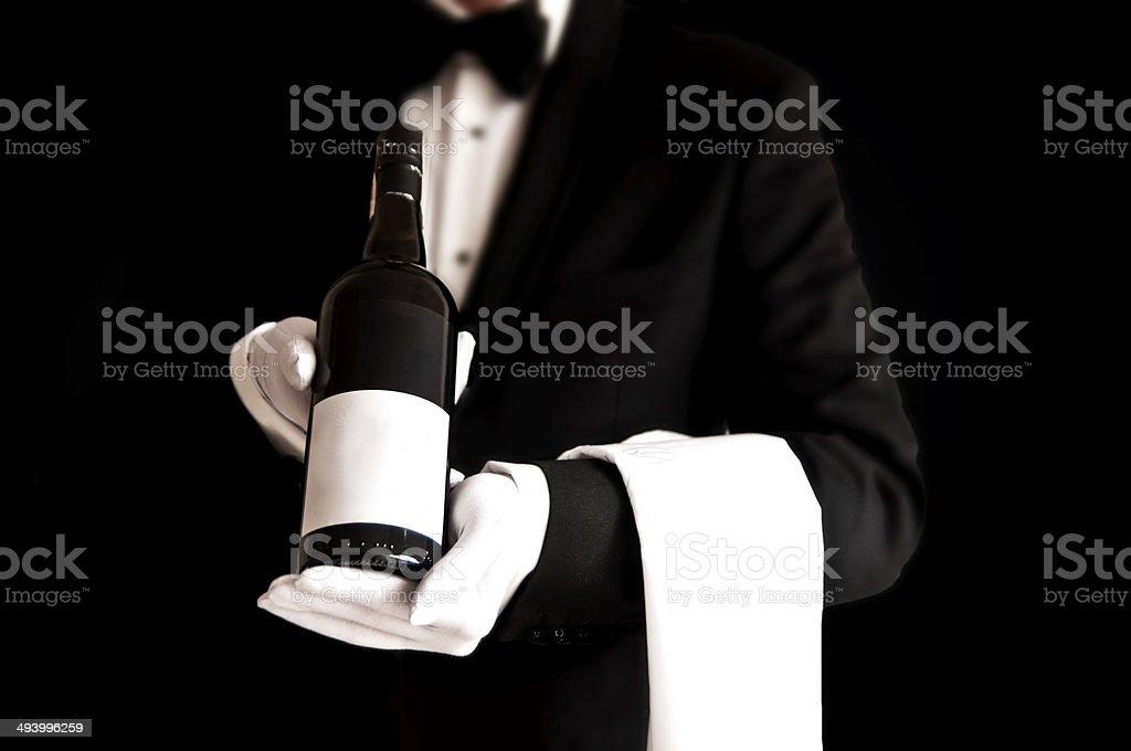 Waiter in tuxedo holding a bottle of red wine stock photo