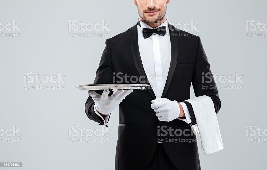 Waiter in tuxedo holding metal empty tray and napkin stock photo