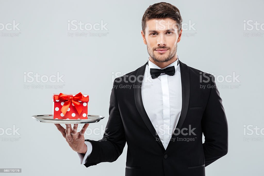 Waiter in tuxedo with bowtie holding present box on tray stock photo