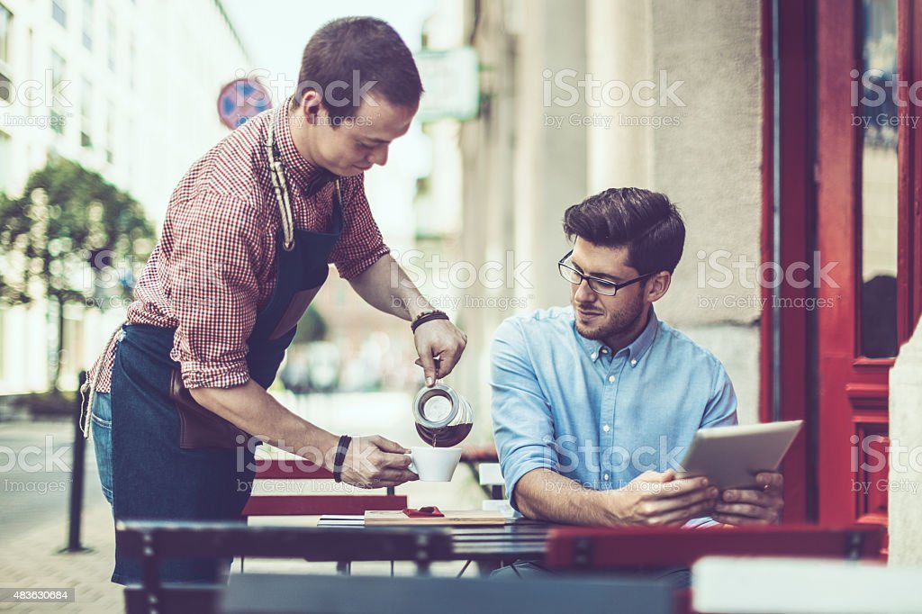 Waiter is serving a coffee to a customer stock photo