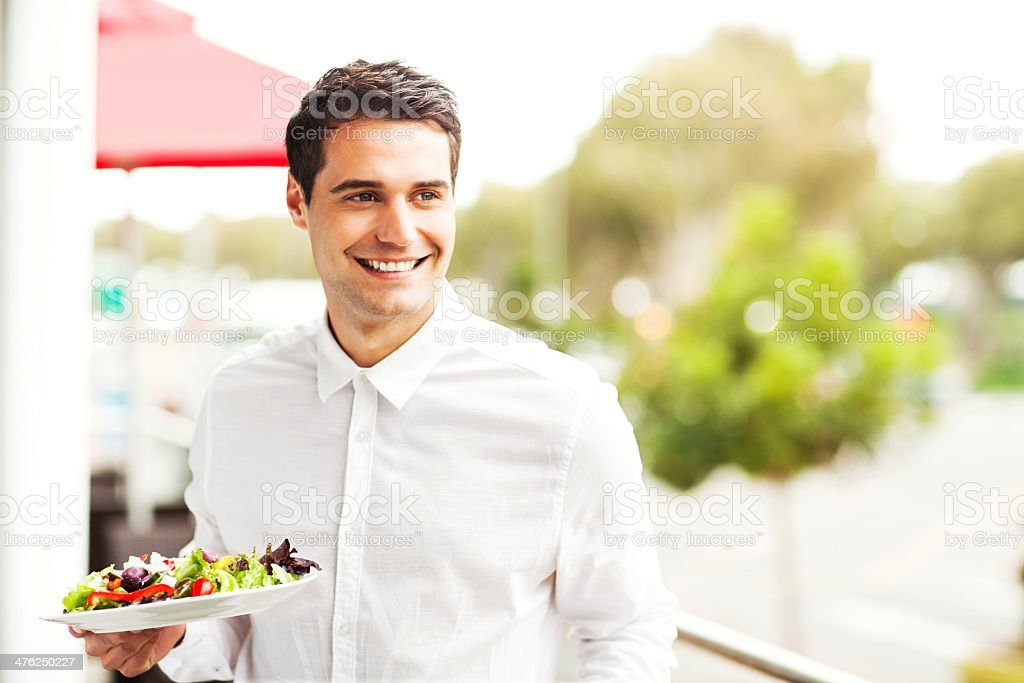 Waiter Looking Away While Holding Salad In Restaurant royalty-free stock photo