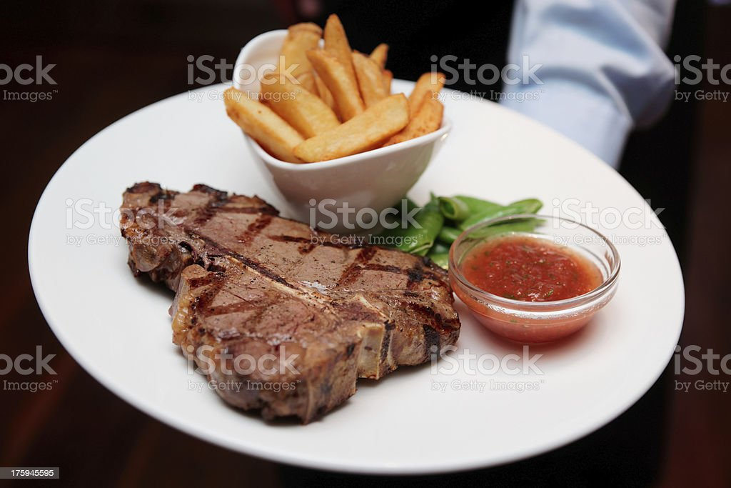 Waiter offering T-bone steak with french fries stock photo