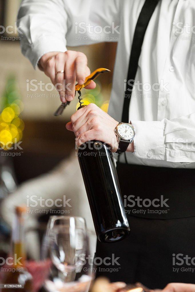 Waiter opening wine bottle stock photo