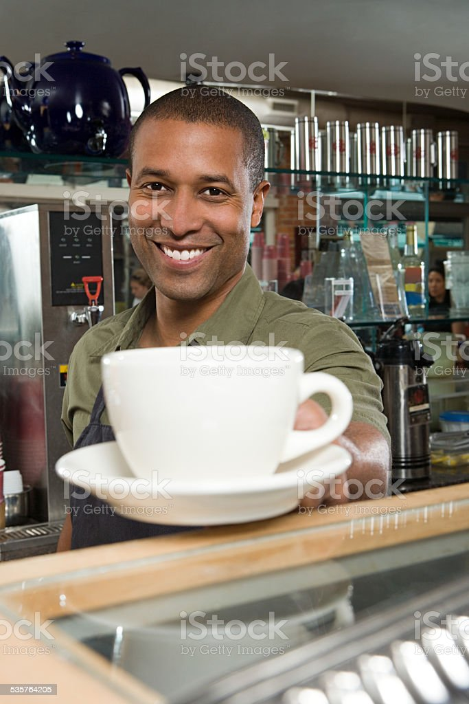 Waiter passing coffee cup stock photo