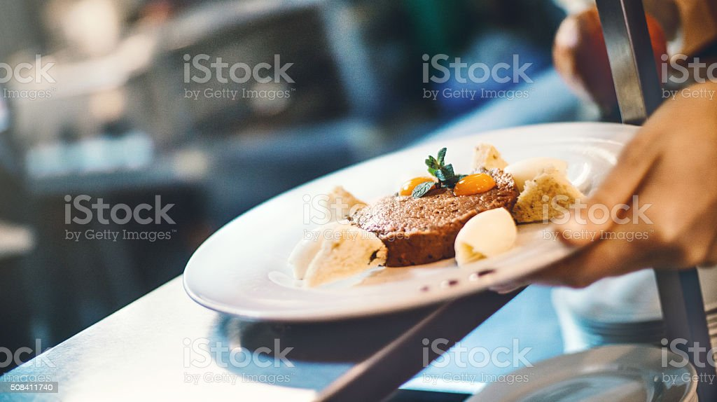 Waiter picking up a meal from serving hatch. stock photo