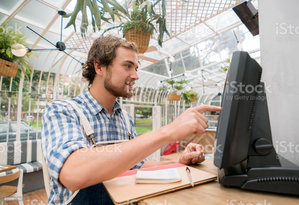 Waiter placing an order on the computer stock photo