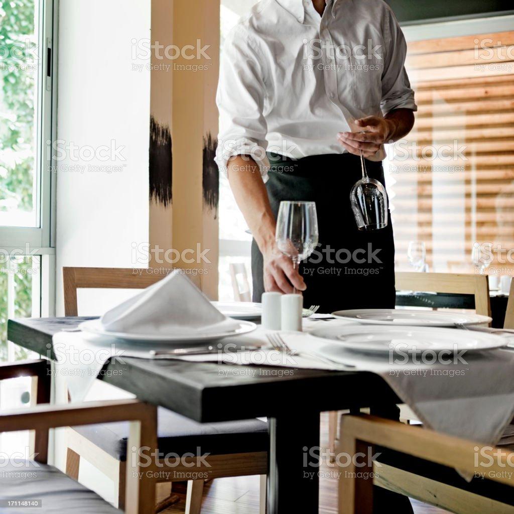Waiter placing glasses on table in restaurant stock photo