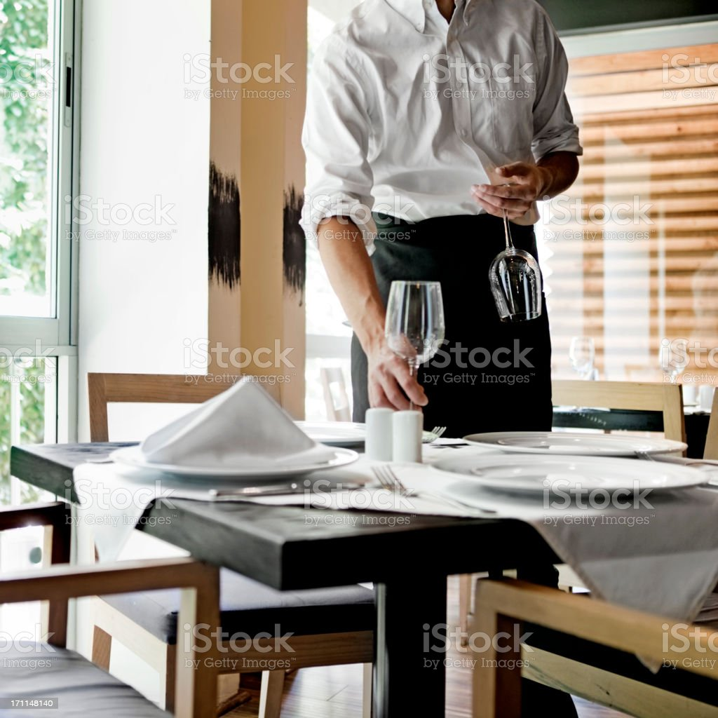 Waiter placing glasses on table in restaurant stock photo