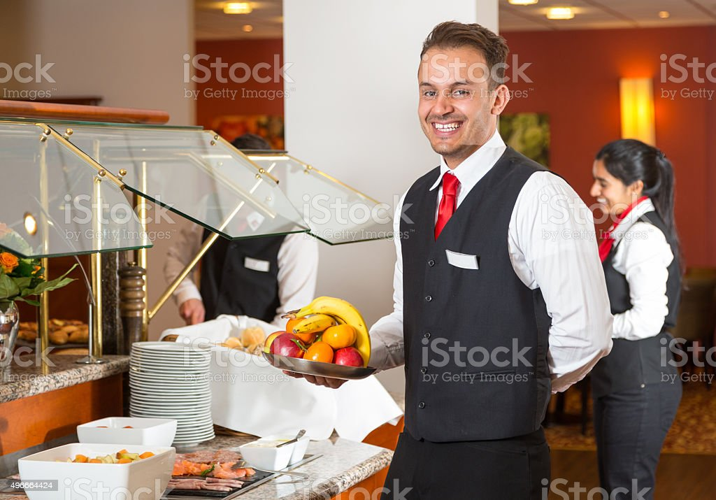 Waiter posing in front of buffet in restaurant stock photo