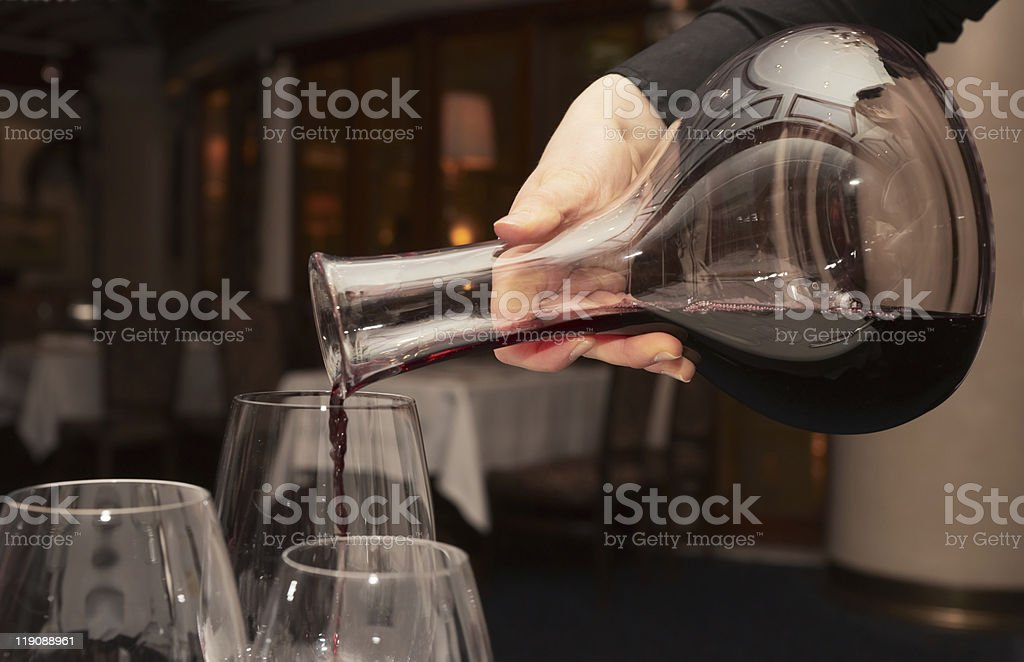 Waiter pouring red wine from decanter stock photo