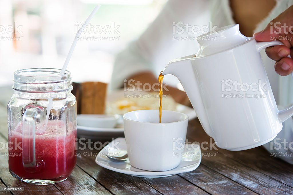 Waiter pouring tea in cup stock photo