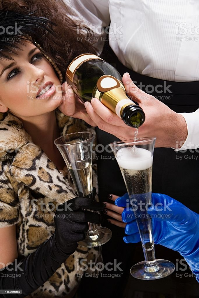 Waiter pouring two women champagne royalty-free stock photo