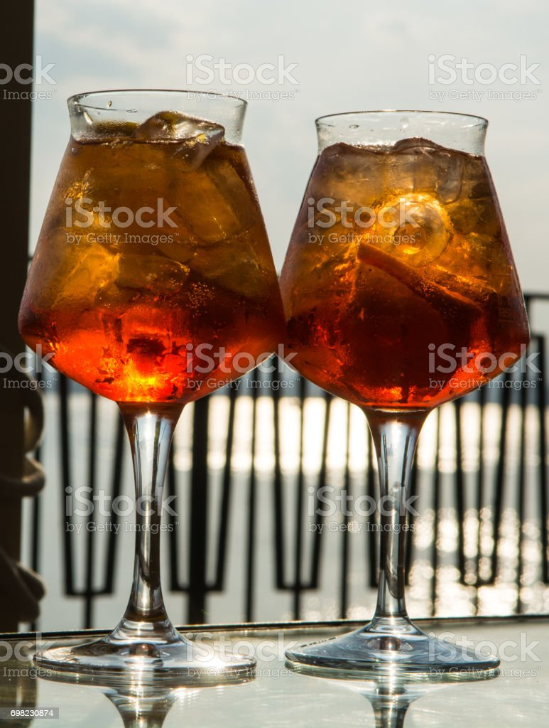 Waiter prepared the Aperol Sprits summer cocktail with Aperol, prosecco, ice cubes and orange in wine glass, ready to drink on sunny terrace stock photo