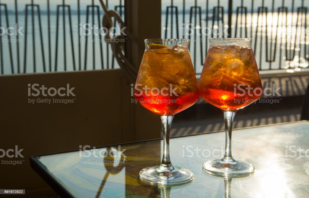 Waiter prepared the summer cocktail with prosecco, ice cubes and orange in wine glass, ready to drink on sunny terrace stock photo