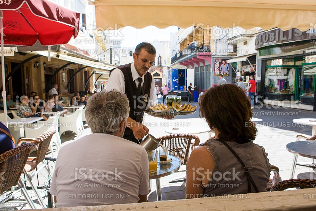 waiter serves milk at Petit Souk Place, Tangier, Morocco stock photo