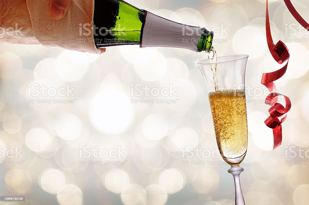 Waiter serving a glass of sparkling white wine with bokeh stock photo