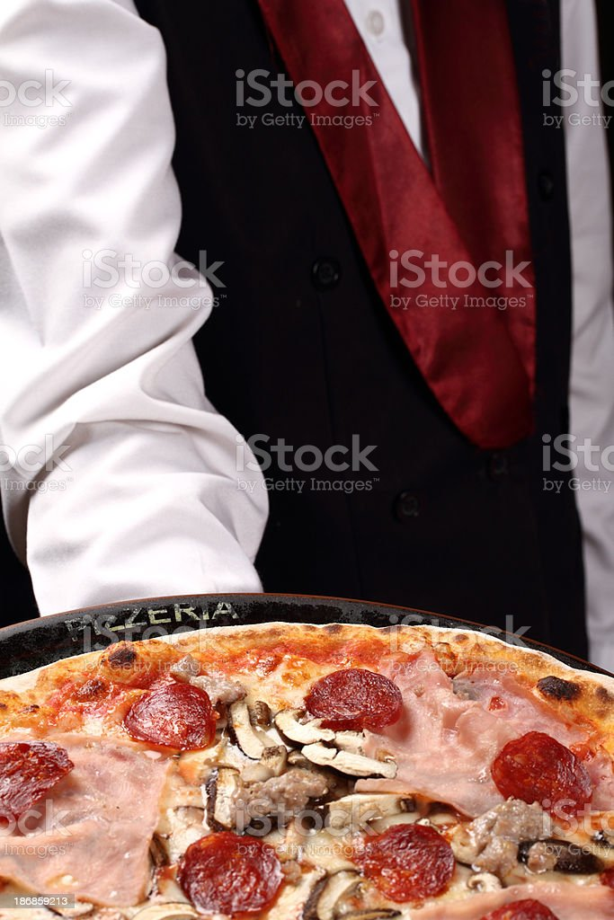 Waiter serving a pizza with ham and salami stock photo