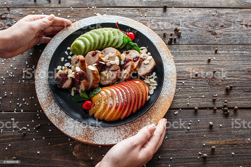 Waiter serving baked veal with fresh fruits stock photo