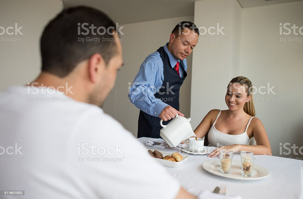 Waiter serving breakfast at a hotel stock photo