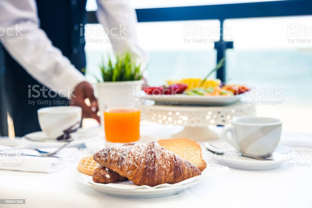 Waiter serving breakfast in hotel room balcony stock photo