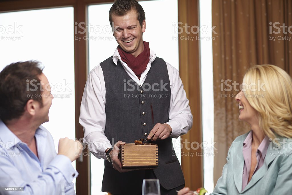 Waiter serving business people in cafe royalty-free stock photo