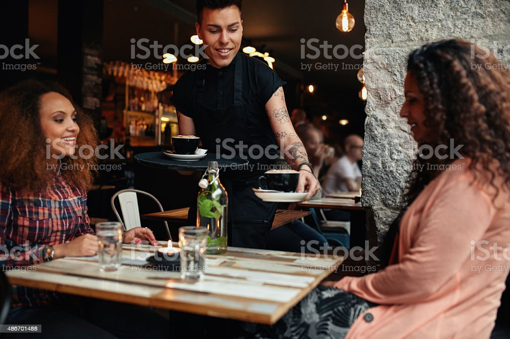 Waiter serving coffee to young women at cafe stock photo