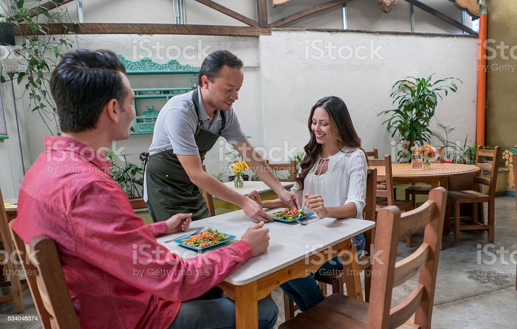 Waiter serving couple at a restaurant stock photo